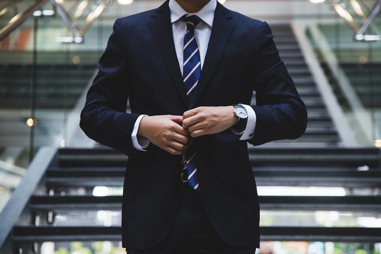 スーツのボタンを留め直すビジネスマン