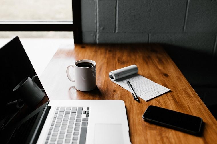 デスクの上に広がるパソコン、スマートフォン、コーヒー